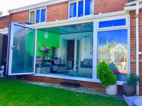 Glass roof conservatory with Bifold Doors white
